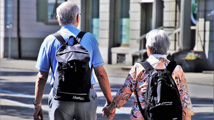 Rentnerpaar hand in Hand mit Rucksäcken